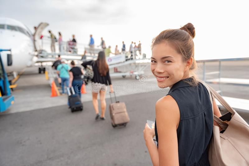 Travel woman boarding airplane at airport. Happy young Asian lady tourist walking on outside tarmac leaving for vacation trip with. Carry-on luggage suitcase stock photos