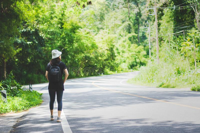 Travel woman with hat and backpack walking on a road royalty free stock photos
