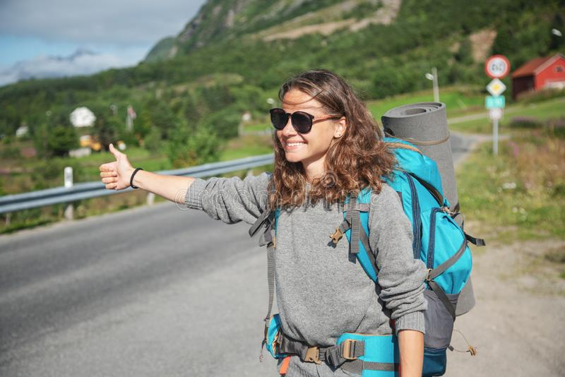Travel woman hitchhiking. Backpacker on road. Happy smiling gorl with big backpack, Norway royalty free stock photos