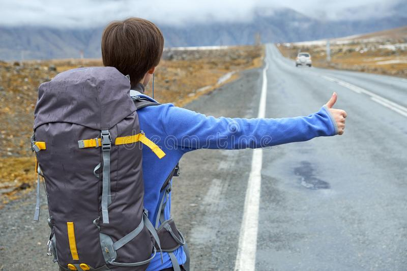 Travel woman hitchhiking. Beautiful young female hitchhiker by the road during vacation trip in mountains stock images