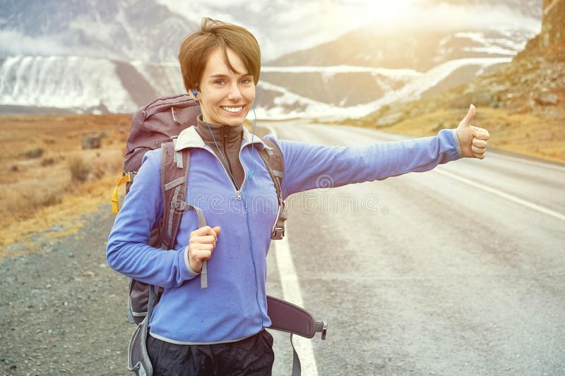 Travel woman hitchhiking. Beautiful young female hitchhiker by the road during vacation trip in mountains at sunset stock image