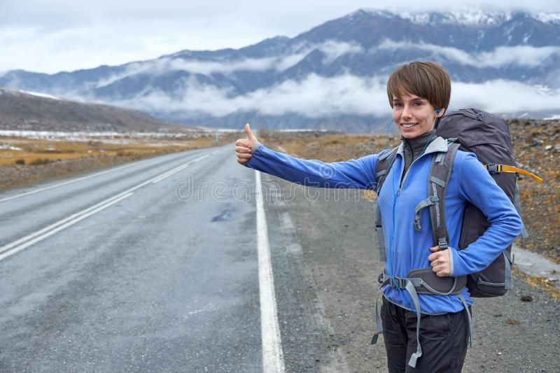 Travel woman hitchhiking. Beautiful young female hitchhiker by t stock photography