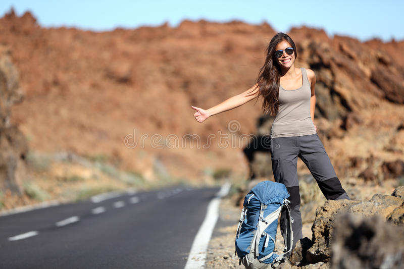 Travel woman hitchhiking on road trip royalty free stock photography