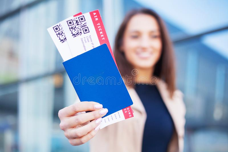 Travel. Woman holding two air ticket in abroad passport near airport royalty free stock photo