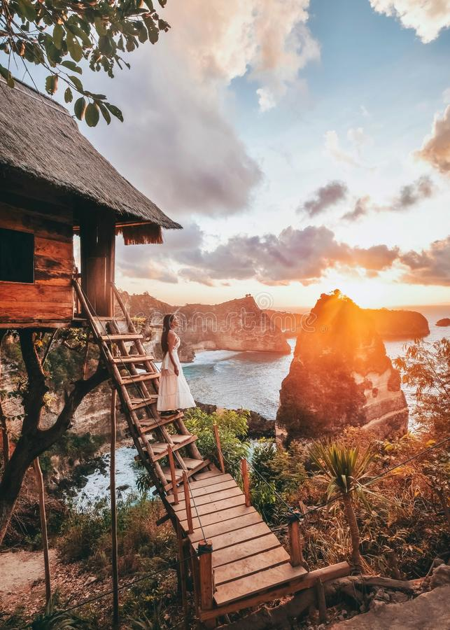 Travel woman looking sunrise view Tree House with Daimond  beach, Nusa Penida island Bali ,Indonesia royalty free stock photography