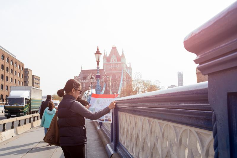 Travel woman looks at the map in front of Tower Bridge in London,UK. royalty free stock photos