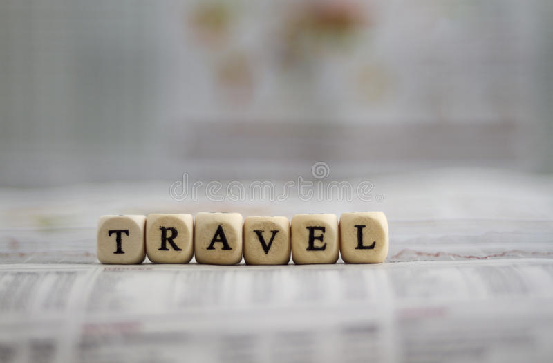 Travel word with cubes on newspaper background stock photo