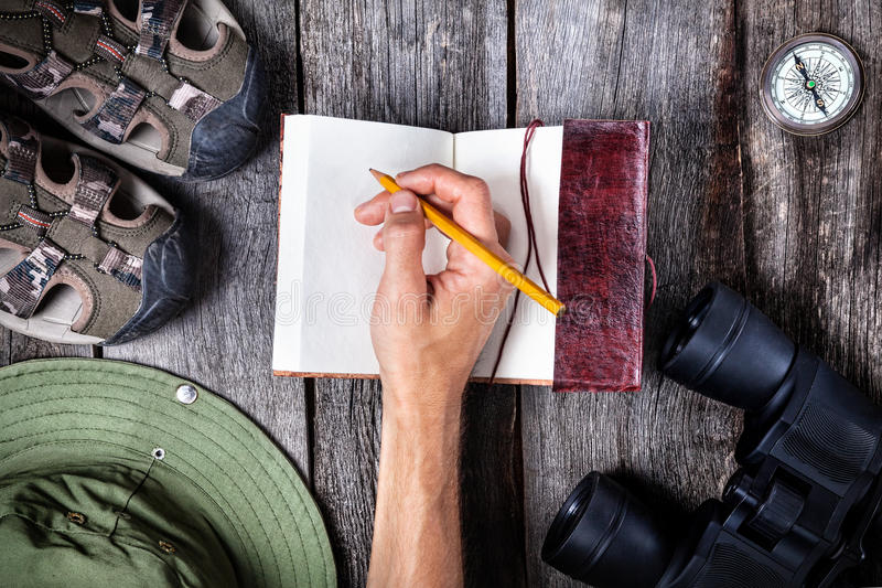 Travel writing. Man writing in the notebook on the wooden table with traveler outfit royalty free stock photo