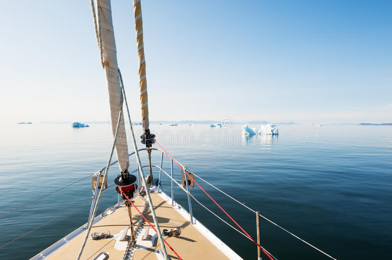Travel by yacht in Greenland. Travel by yacht in the Atlantic ocean among the icebergs in Greenland stock photos