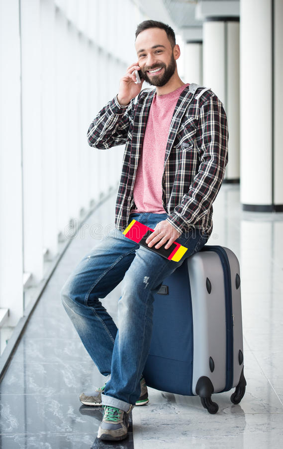 Travel. Young man with a suitcase and passport ready to travel. He is speaking by phone stock photography