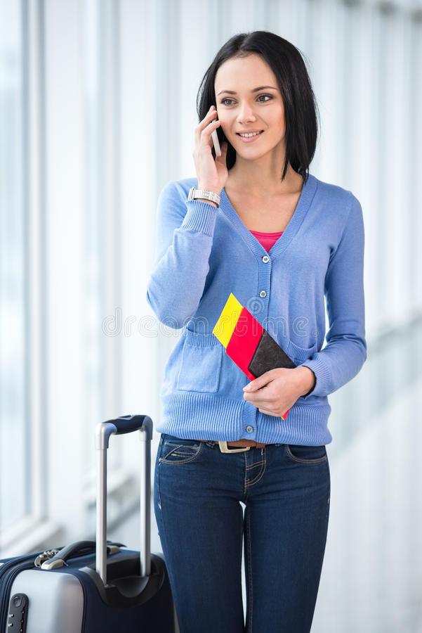 Travel. Young smiling woman with a suitcase and passport is ready to travel royalty free stock photography