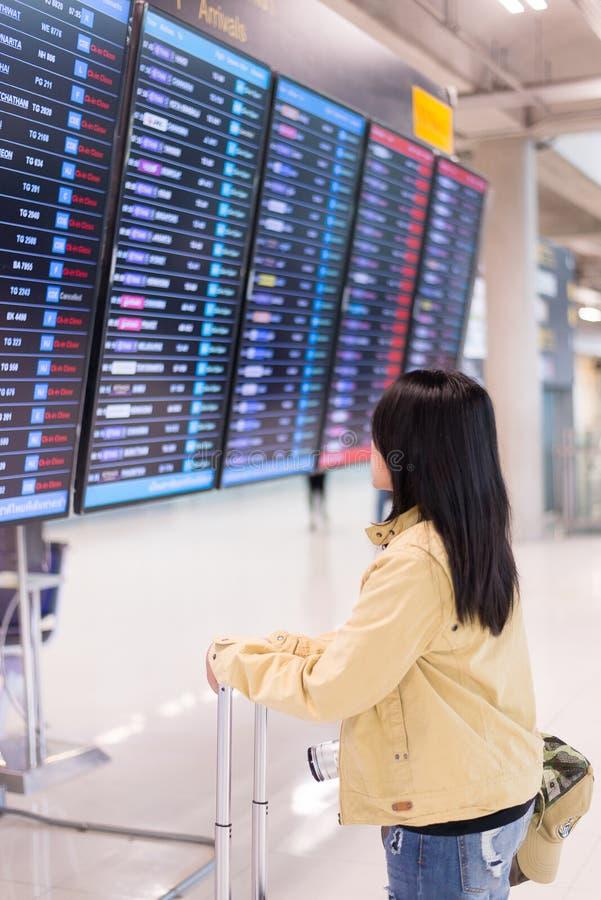 Travele asiático bonito da mulher que está na placa da informação do voo no aeroporto foto de stock royalty free