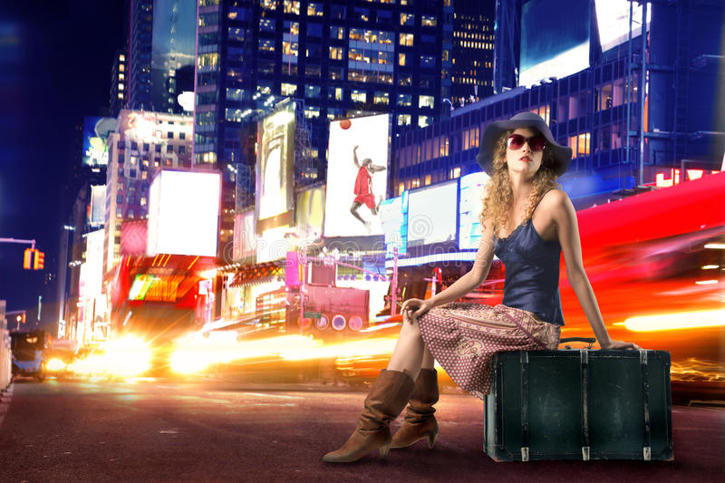 Traveler. Woman seated on suitcase in Time Square stock photos