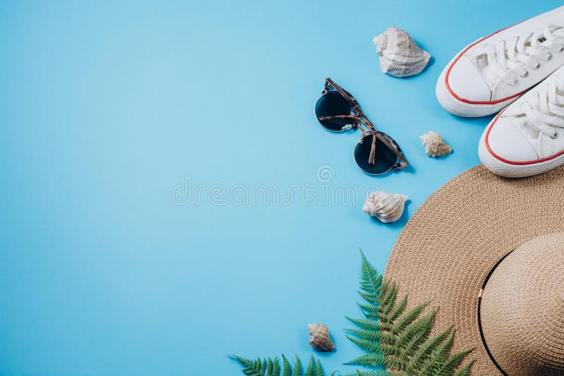 Traveler accessories, tropical fern leaf branches, hat, sunglasses, footwear and seashell on blue background. Travel vacation stock photography