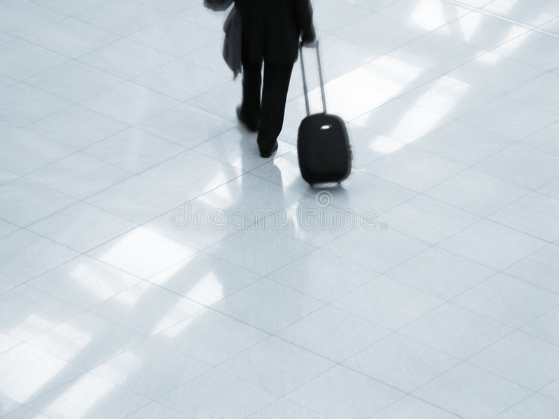 Traveler at airport. Air traveler at an airport. A motion blur (center at the traveler) overlies the image royalty free stock image