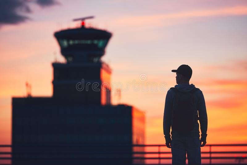 Traveler at the airport. Silhouette of the traveler at the airport. Air Traffic Control Tower at the amazing sunset. Prague, Czech Republic stock image