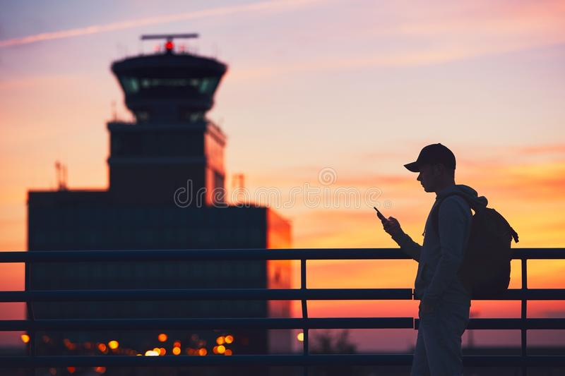 Traveler at the airport. Silhouette of the traveler with mobile phone at the airport. Air Traffic Control Tower at the amazing sunset. Prague, Czech Republic royalty free stock photo