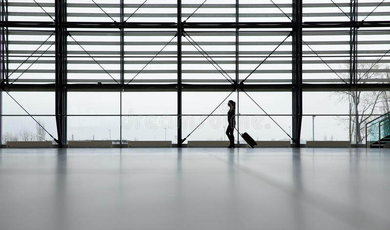 Traveler in airport terminal. Woman walking in airport terminal with her roller bag stock photography