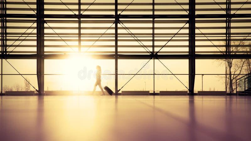 Traveler in airport terminal. Woman walking in airport terminal with her roller bag in late evening sunset stock image