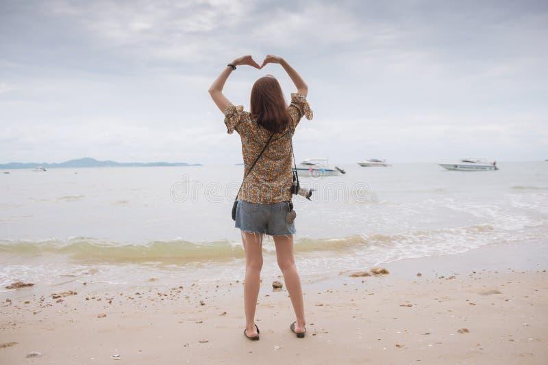 Traveler asian girl holding a heart shape. Traveler asian girl holding a heart shape on the sea royalty free stock images