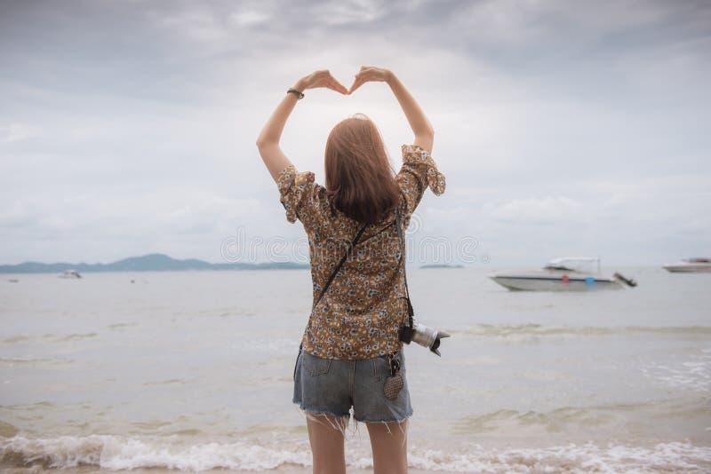 Traveler asian girl holding a heart shape. Traveler asian girl holding a heart shape on the sea stock images