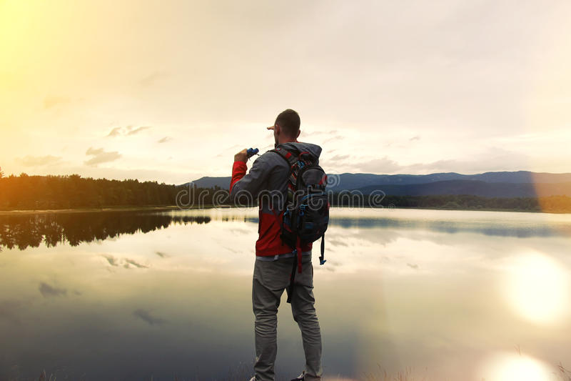 Traveler with a backpack and binoculars looking at the lake stock images