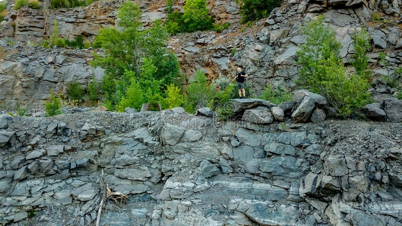 A traveler with a backpack on his shoulders is standing near breakage of cliff on the stone. Tourist is posing on the stock photography