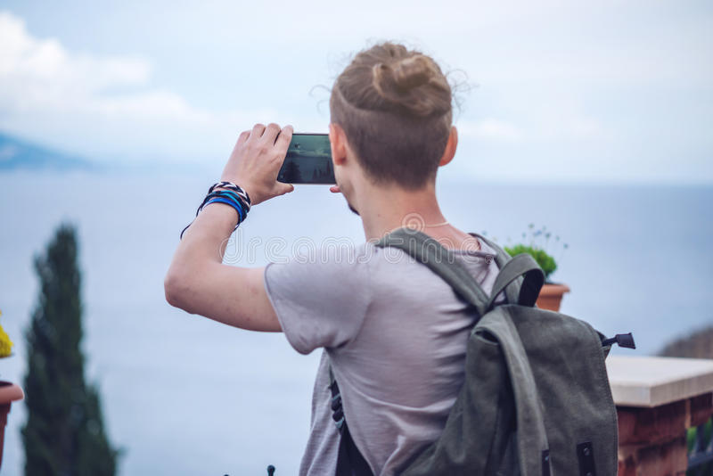 Traveler with backpack makes a photo on your smartphone outdoors with mountains in the background stock image