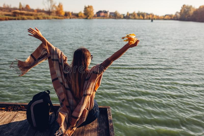 Traveler with backpack relaxing by autumn river at sunset. Young woman raised arms feeling free and happy stock photos