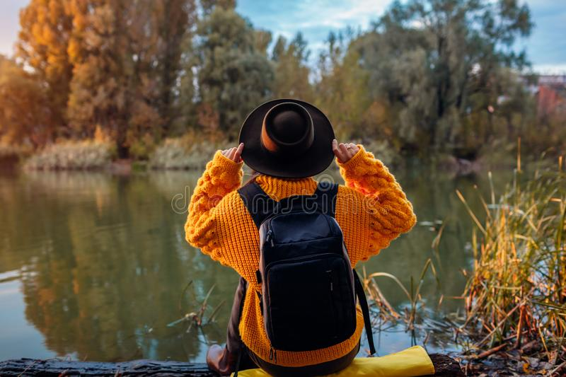 Traveler with backpack relaxing by autumn river at sunset. Young woman sitting on bank and relaxing holding hat stock photos