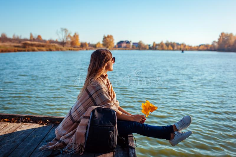 Traveler with backpack relaxing by autumn river at sunset. Young woman sitting on pier admiring landscape royalty free stock images