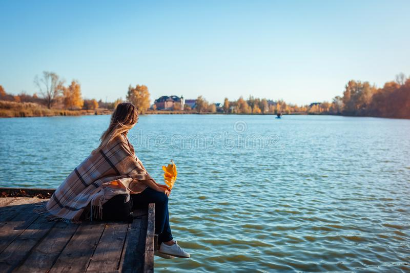 Traveler with backpack relaxing by autumn river at sunset. Young woman sitting on pier admiring landscape royalty free stock photo