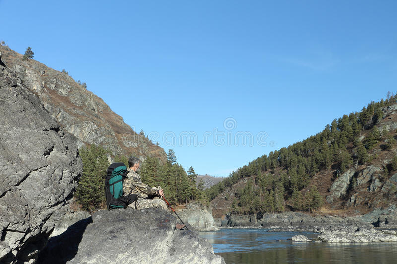The traveler with a backpack sitting on a stone on the river bank royalty free stock photography