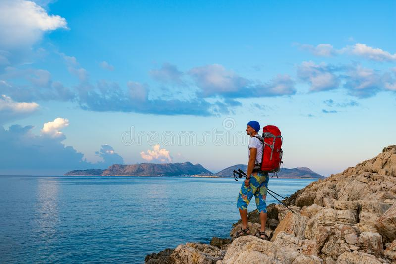 Traveler with backpack stands on the rock seashore stock image