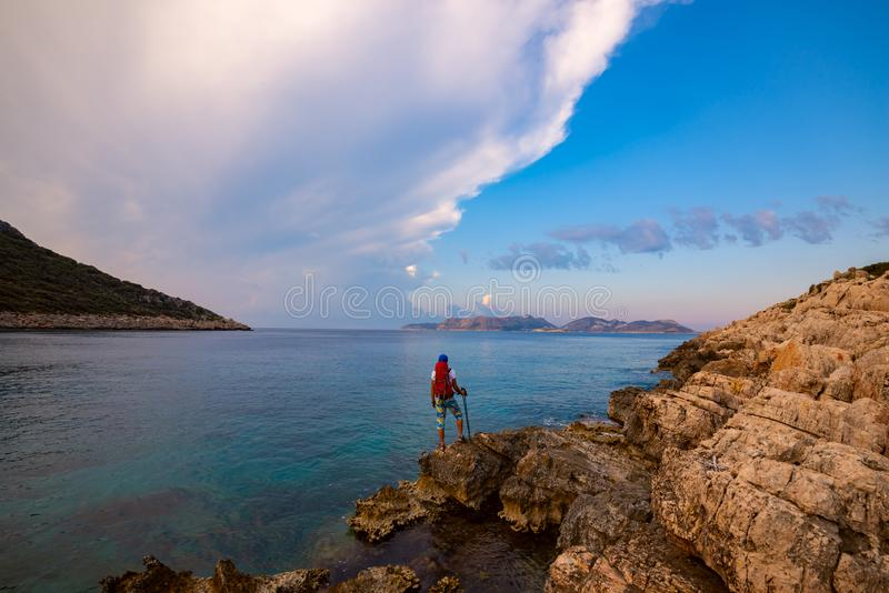 Traveler with backpack stands on the rock seashore royalty free stock photography