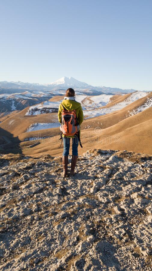 Traveler with a backpack. The view from the back. In the background, the beautiful mount Elbrus. Single independent trip around stock photography