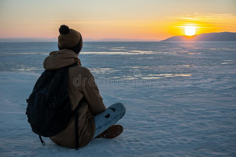 Traveler with a backpack watching the sunset on the snowy ice of lake Baikal. Concept of freedom and travel stock image