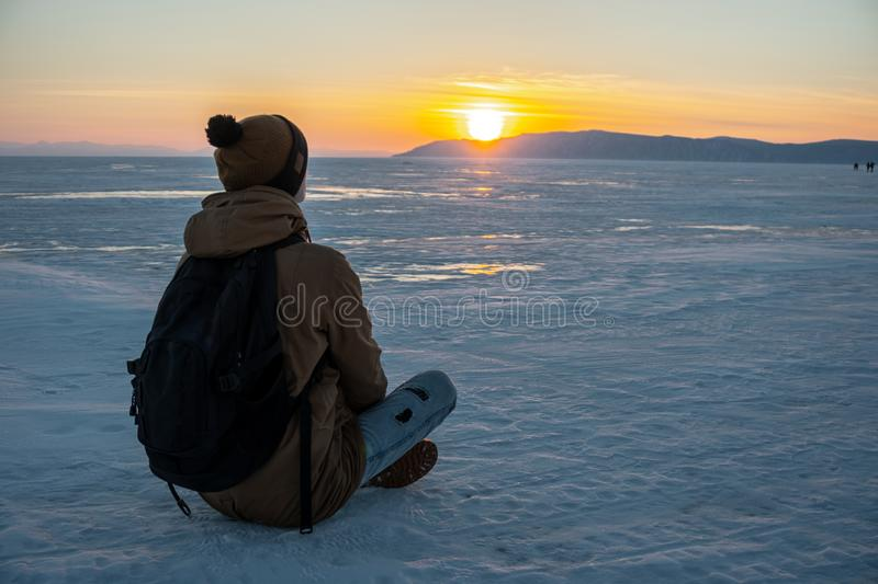 Traveler with a backpack watching the sunset on the snowy ice of lake Baikal. Concept of freedom and travel royalty free stock images