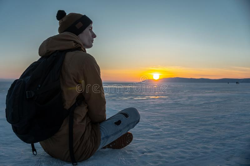 Traveler with a backpack watching the sunset on the snowy ice of lake Baikal. Concept of freedom and travel royalty free stock photography