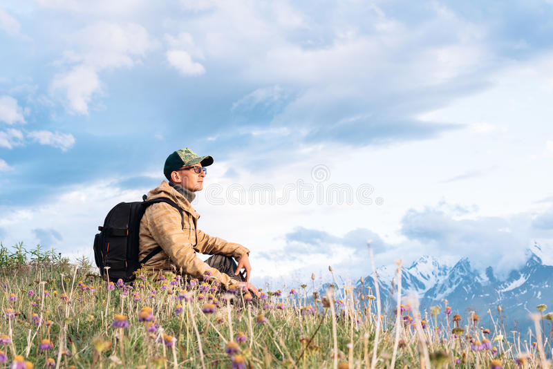 Traveler with a backpack and wearing cap glasses sitting o stock images