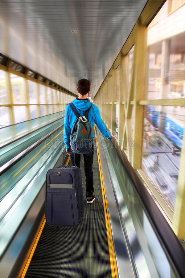 Traveler Beginning Journey. Young tourist with a backpack and a suitcase moving on the escalator at the railway station. Motion Blur