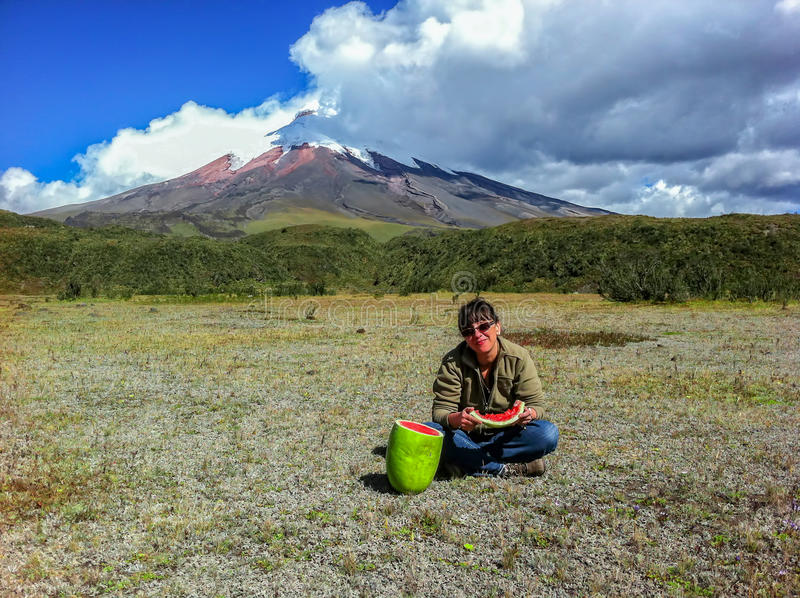 Traveler Caucasian woman eating a watermelon, Cotopaxi volcano stock photography