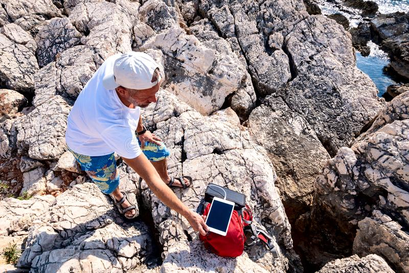 Traveler charges the tablet using a solar battery. Attached to a backpack on a rocky seashore - adventure travel along Lycian way, Turkey. Top view royalty free stock image