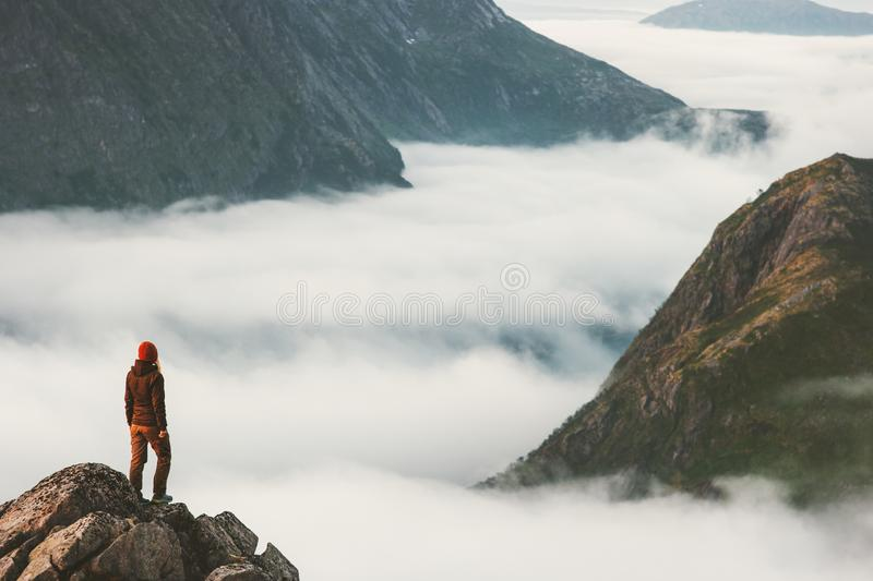 Traveler on cliff overlooking mountain clouds alone. Hiking adventure journey outdoor Norway vacations traveling lifestyle weekend getaway royalty free stock photography