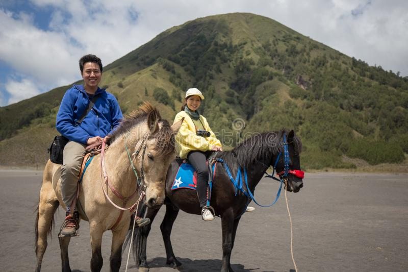 Traveler couple ride a horse at Mt. Bromo, east Java, Indonesia. royalty free stock images
