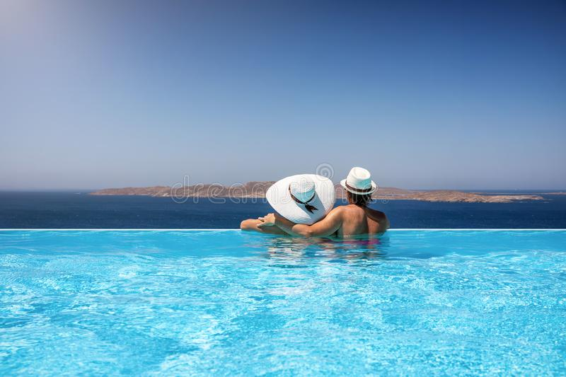 Traveler couple in a infinity pool enjoying the Mediterranean sea. Traveler couple with sunhats hugging in a infinity pool and enjoy the view to the stock photography