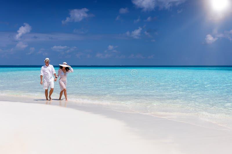 Traveler couple walks down a tropical beach stock images