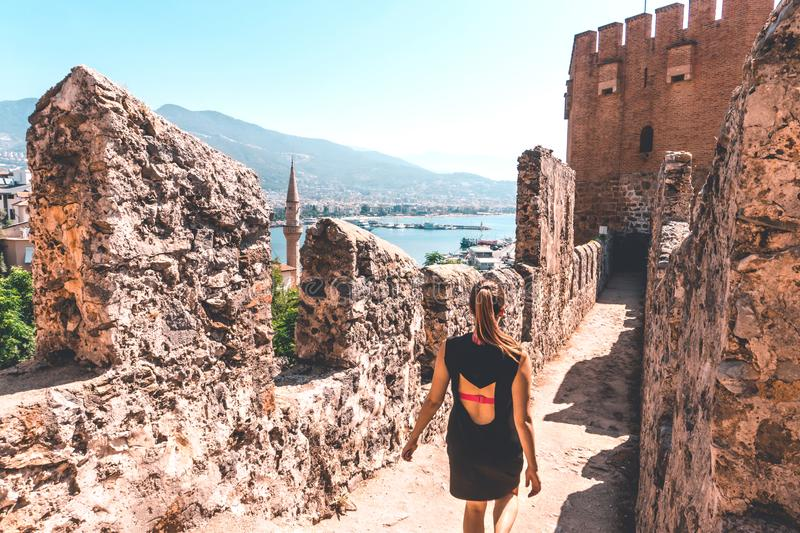 Traveler exploring the city of Alanya in Turkey. Woman walking and discovering old landmark in Europe. royalty free stock photo