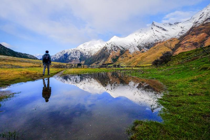 Hiker exploring natural landscape image of snow mountain, blue lake in New Zealand royalty free stock photo