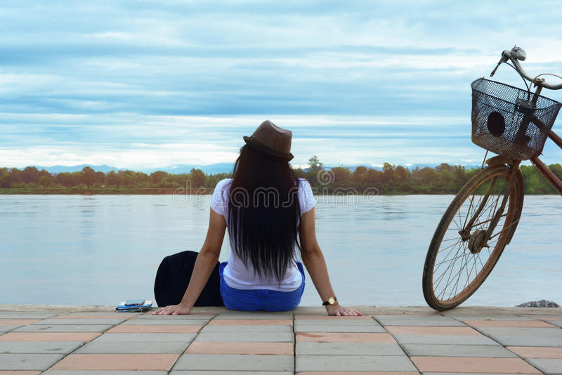 A traveler girl with bag and bicycle sitting on cement ground royalty free stock photo